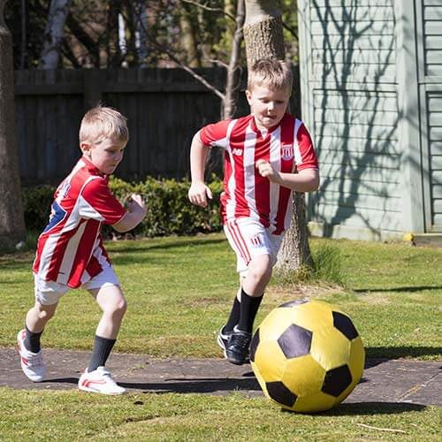 two boys playing footbll in the yard with the stoke city shirts on