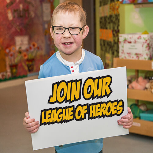 a boy holding a League of Heroes banner