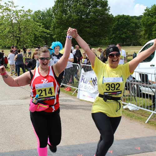 Two ladies cheering with their hands in the air after completing run